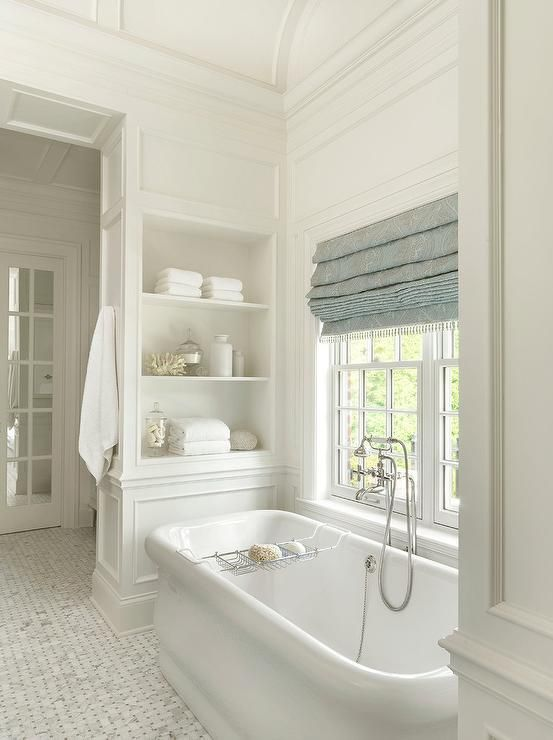 Well appointed bathroom boasts a tub nook positioned under a barrel ceiling and fitted with a Waterworks Empire Freestanding Rectangular Bathtub with a polished nickel antique tub filler placed on marble basketweave floor tiles beneath a window dressed in a blue tassel roman shade.