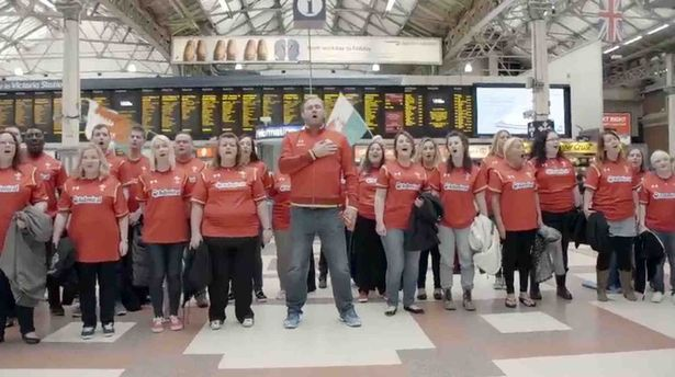 Scott Quinnell leads the choir at London's Victoria station