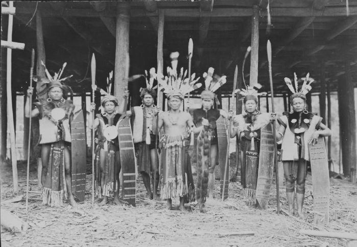 COLLECTIE TROPENMUSEUM Een Bahau Dajak hoofd met gevolg in krijgsuitrusting Midden-Borneo.