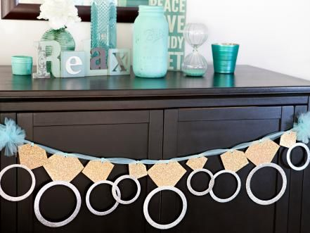 We say YES to this giant diamond ring banner; the perfect decor for a bachelorette party or bridal shower. It is easy to make and so sparkly sweet. You will need glitter paper, eyelets, an eyelet setter, ribbon and scrapbooking adhesive. Download the diamond shape and the ring shape, print, and then cut out the diamonds. Attach each circle to the diamond using scrapbooking adhesive. Set an eyelet in each ring then insert the ribbon or tulle through the eyelet hole. Hang and celebrate!