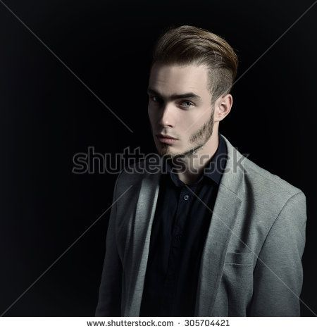 Portrait of attractive mysterious young man over black background.