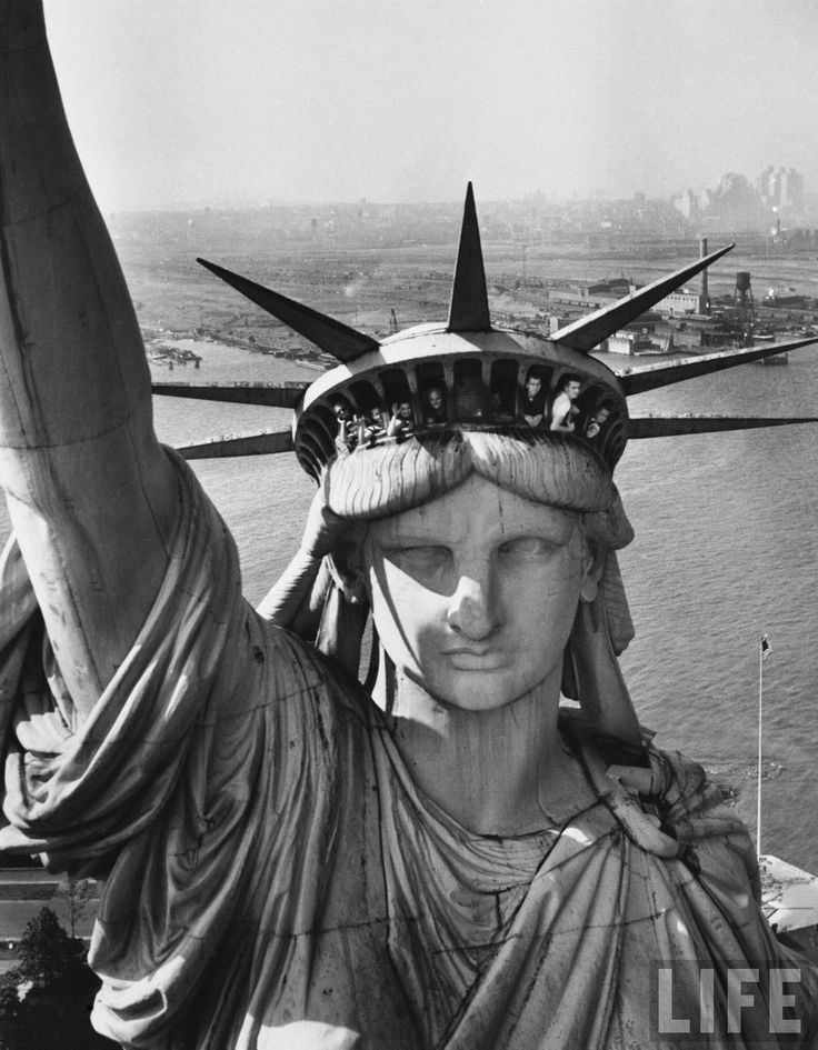 Margaret Bourke-White: Sightseers hanging out of the windows in the crown of the Statue of Liberty with the NJ shore in the background. 1951