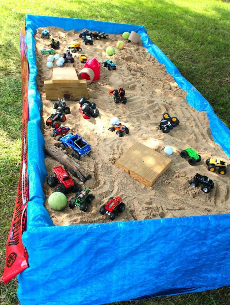 Monster truck sensory table. We took two pallets and nailed them together. Took the top slates out and set on top of 6 center blocks. Draped a tarp over the pallets and added sand! Wah la!