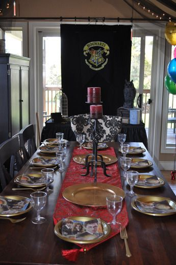 Harry potter table decorations - LOVE the Hogwarts Crest and the black tulle with lights above the table