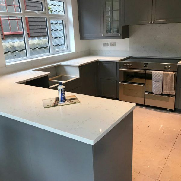 This is the Attica White Carrera style Quartz that has just come onto the market. There is limited stock so check it out today! It is a white marble effect with a blue vein throughout. It looks stunning against this grey/ blue style cabinetry kitchen.