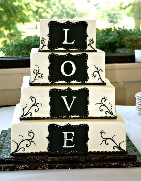 "This whimsical black and ivory decorated wedding cake is made of elegant designs and a four tiered sign spelling out our favorite word ""LOVE"". A great wedding c"