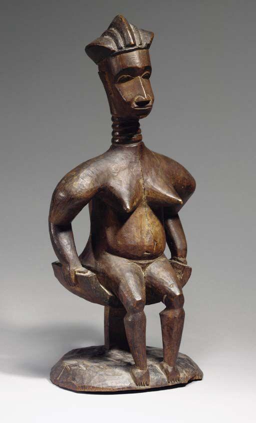 STATUETTE BIDJOGO  Etikoka, Guinée Bissau  Représentant une femme sur un tabouret traditionnel Bidjogo à l'assise incurvée, les mains posées sur les bords du siège, les larges épaules surmontées par un cou annelé et une tête allongée avec un visage aux traits réalistes finement sculptés, la coiffure composée de cinq tresses rejettées vers l'arrière, les pieds suivant la courbure de la base ovale. Patine sombre avec certains éléments rehaussés de noir. Hauteur: 43 cm