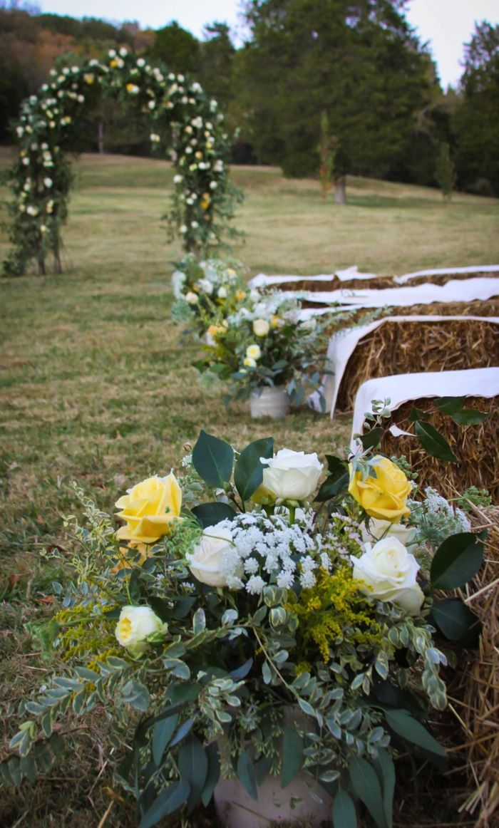 Who wouldnt want to be a guest at this wedding? I love the hay bails and greens and buckets of flowers!    www.cedarwoodweddings.com