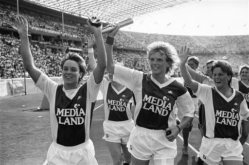 Celebrating with the Women's DFB Cup (German Soccer Cup) on June 24, 1989 in Berlin, Germany are members of the German football club TSV Siegen, from left to right: Martina Voss, Andrea Haberless and Silvia Neid. Their team defeated FSV Frankfurt 5:1. (AP Photo/Rainer Klostermeier)