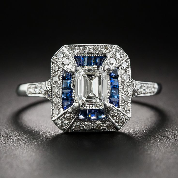 A gorgeous, classically fashioned vintage emerald-cut diamond, weighing .69 carat and accompanied by a GIA Diamond Grading Report stating: I color - VS1 clarity, radiates from within a much newer Art Deco style home recently crafted in 18K white gold, royal blue calibre sapphires and small full-cut diamonds