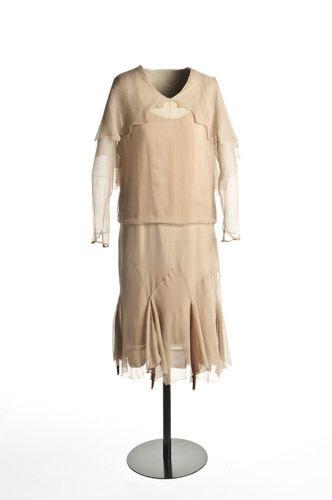 Vestido   1925-1930  Los años 20 supusieron un cambio radical en la imagen de la mujer y este vestido realizado con crespón de seda beis es un buen ejemplo de ello. La silueta ahora es recta y evita así que se marquen caderas, cintura y pecho, con lo que el cuerpo de la mujer se convierte en un cilindro. Por otra parte, la mujer comienza a enseñar más su cuerpo, especialmente las piernas, ya que las faldas progresivamente se van acortando hasta llegar a la rodilla, como en este ejemplo. En…