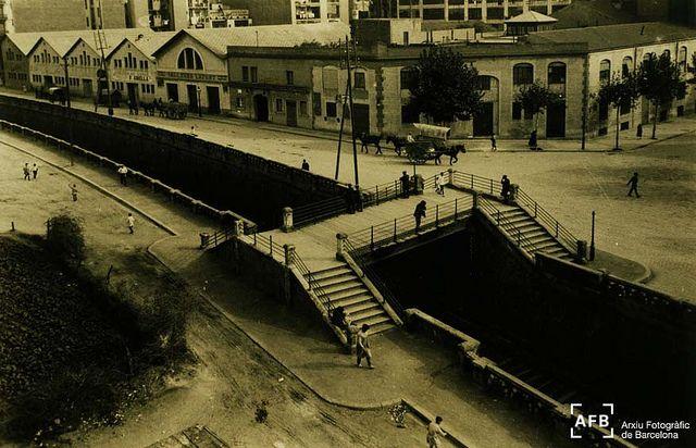 """""""Pont del Mico""""    La fotografia és a la cruïlla d'Aragó amb Avinguda Roma i carrer Casanovas, i està presa al voltant dels anys 30 del segle XX, quan el carrer Aragó encara no estava cobert, i hi circulava el tren que actualment encara hi passa. El pont que creua les vies era conegut com el """"Pont del Mico""""."""