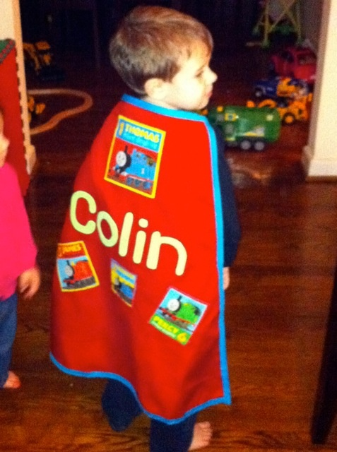 "I made this cape from scratch. I went to the fabric store with my three-year old son. He picked out the material. I used the other cape Jaxson received as a gift as my pattern and made modifications. I thought the original cape was a bit long, so I shortened it. I wish I had taken photos along the way, but I didn't. I let my son help me do the sewing. He would help push the fabric. He thought it was great fun.    Tools and materials needed - Red fabric for the cape; ""Thomas"" fabric for the…"