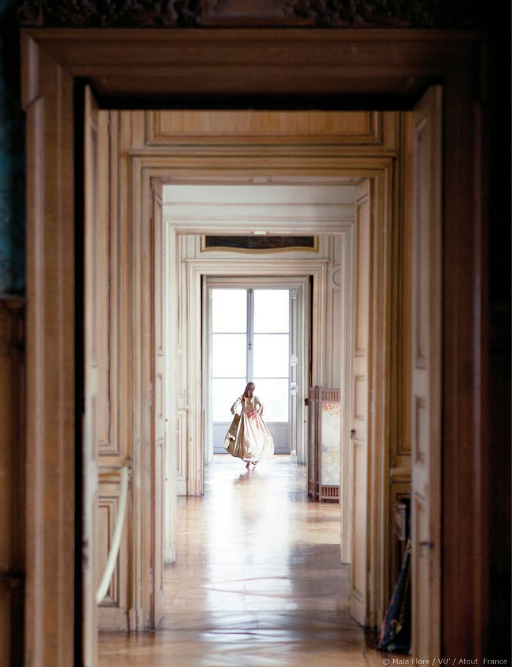 Running away, or running to? Visual writing prompt | Lady with gorgeous white ball gown in long French mansion corridor | Scene setting inspiration for romance, fantasy and historical book writing | Sunny house photography