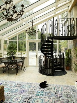 Cast Iron table and chair set, Cast Iron spiral staircase, beige tile floors, area rug, sunroom, chandeliers, plants, natural light, black cat.