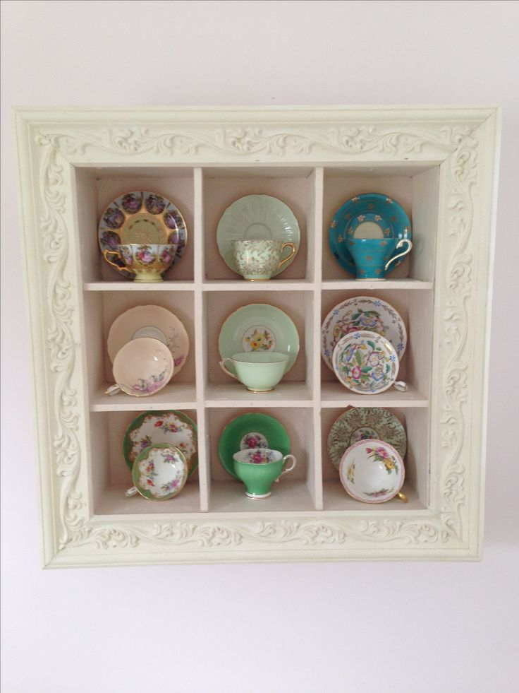 Display of tea cups in vintage looking framed wall display