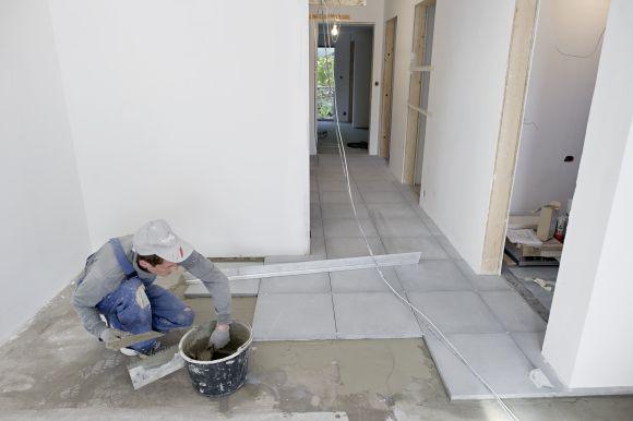 Arbeidene med å legge betongfliser i gangen er godt i gang.