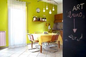 La paretina lavagna e il lampadario di riciclo si affiancano bene alle sedie di design.