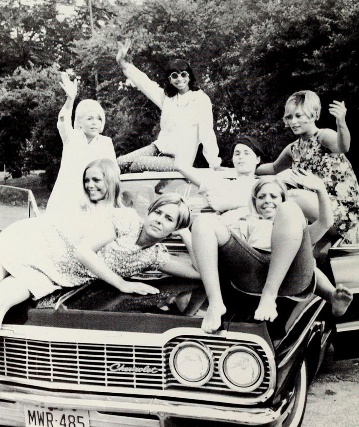 Barefoot swinging-sixties girls on the hood of Chevrolet, 1968