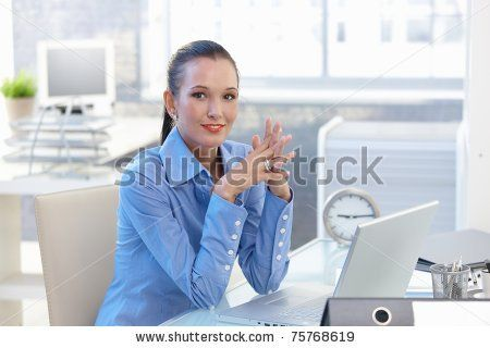 stock photo : Portrait of happy office worker girl sitting at desk, smiling, looking at camera.