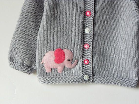 Chaqueta gris plata muy lindo del bebé con diseño de elefante rosa y botones de flores de plástico. La chaqueta es suave y fino pero cálido. Perfecto para la temporada de primavera/otoño aún más para los días de verano frío. Un buen regalo para sembrador de bebé.  Material: Lana de merino 100% suave de alta calidad  Tamaño de imagen: 12-18 meses  Cuidado: lavado a mano  Cada elemento de Tutto es tejen a mano y hecho a pedido. Puede elegir los colores, tamaño y diseño que usted desee.  Puede…