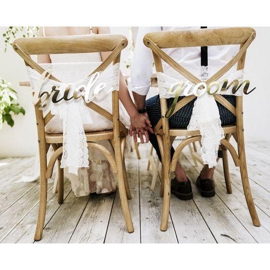 Bruidspaar stoeldecoratie Bride and Groom. Goudkleurige stoelversiering bordjes Bride en Groom. Formaat: ongeveer 35 x 17 cm en ongeveer 37 x 17 cm. U ontvangt 1x Groom en 1x Bride.