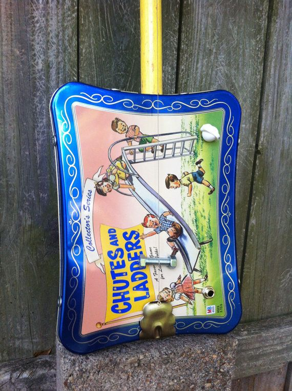 This one string, electric Diddley Bow is a handmade on-of-a-kind instrument made from an upcycled classic Chutes & Ladders game tin. The yellow broom handle neck was made from an old broom that was found hanging on the back porch of an abandoned farmhouse.The tailpiece was custom made from a pair of thrift store salad tongs. I used bolts for the bridge and nut, and an open back vintage style tuner. There is a piezo pickup inside wired to a volume pot with a mini chickenhead knob for playi...