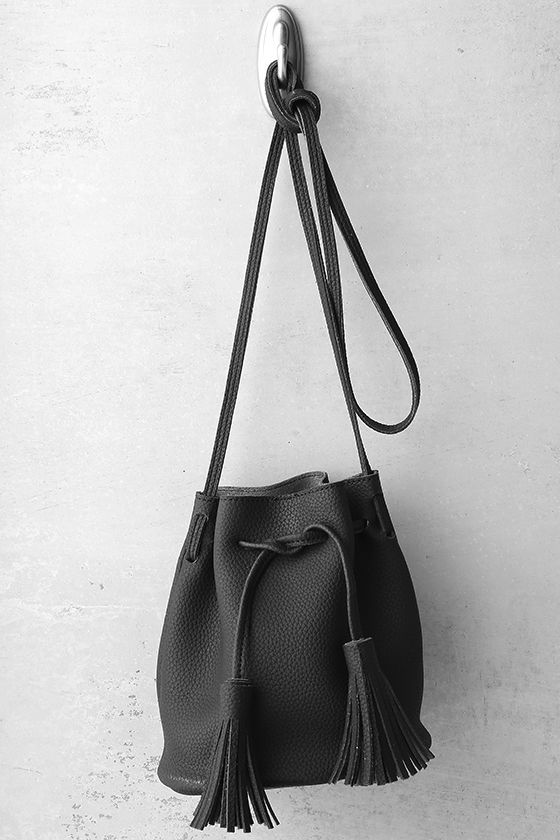 """Put all your essentials in the Mercy Black Mini Bucket Bag and head to the VIP! Pebbled vegan leather forms this versatile bucket bag with a crossbody design, and a drawstring top with tasseled ends. Faux suede interior. Shoulder strap measures 50""""."""