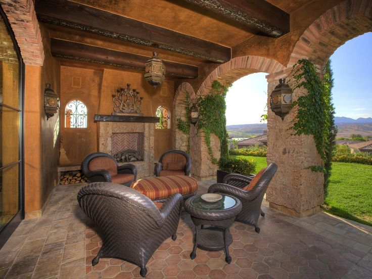 This Italian-flavored patio features arched brick access points, hexagonal tile floor, four chairs with ottoman and glass side table, exposed ceiling beams, ornate chandelier and outdoor fireplace.