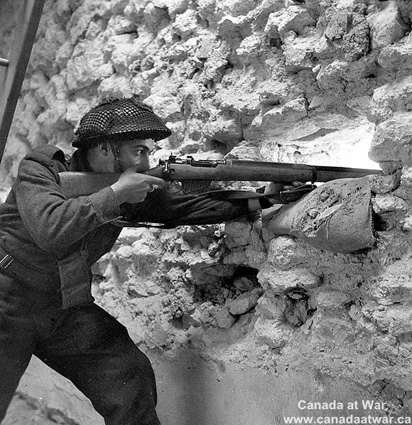 Canadians capture Caen - Rifleman R.R. Schwabe mans a loophole in French barracks used by the Germans and captured by the Regina Rifle Regiment. July 23, 1944, Vaucelles, France.