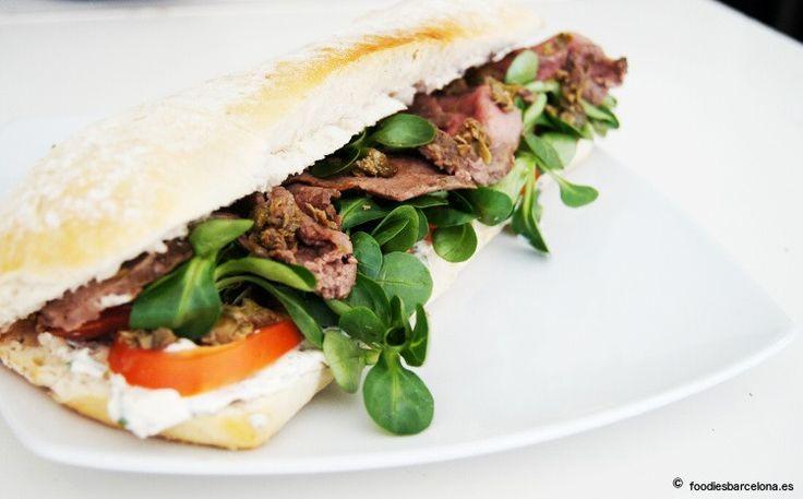 Sandwich con roast beef de ternera en finas lonchas, tomate raf y canónigos, con pasta de alcaparras y anchoas y un toque de mostaza