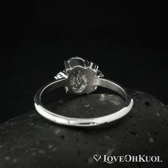 With classic details and a modern twist, this Rose Cut Salt & Pepper Diamond cluster ring brings the best of both worlds to your eternal yes. The rose cut oval center stone has a 0.61 carat weight and natural salt and pepper inclusions that give it a modern, ethereal vibe. Accented with side rose cut diamonds that resemble a crown, these stones add an extra 0.06 carats of sparkle to the unique piece. This engagement ring can be customized with your choice of setting, whether 14kt white, r...