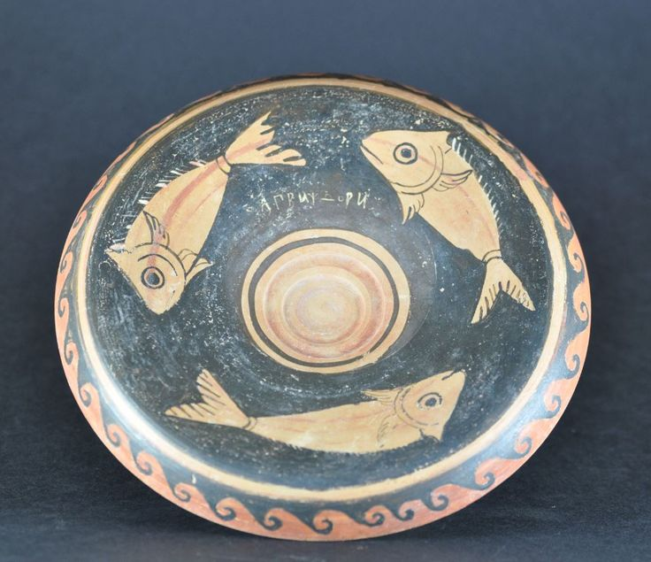 Greek fish plate with inscriptions, 4th century B.C. Western Greek, probably Sicily, red figure fish plate with three fish and painted inscription before firing, on the back another inscription after firing, 18.5 cm diameter. Private collection