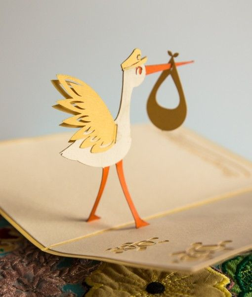 The front of this yellow pop-up card features a laser-cut illustration of a flying stork on its way to make an important delivery. Open this adorable baby announcement card to find a surprising delive                                                                                                                                                     More