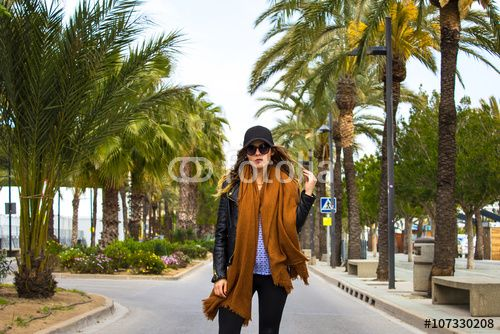 Classy girl standing on the tropical road with palm trees