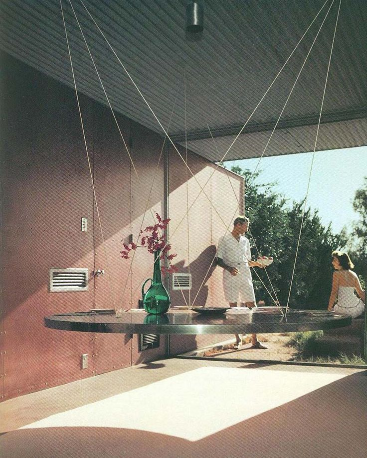 Albert Frey with his floating dining table suspended by cables from the ceiling -    photo by Julius Shulman - 1960