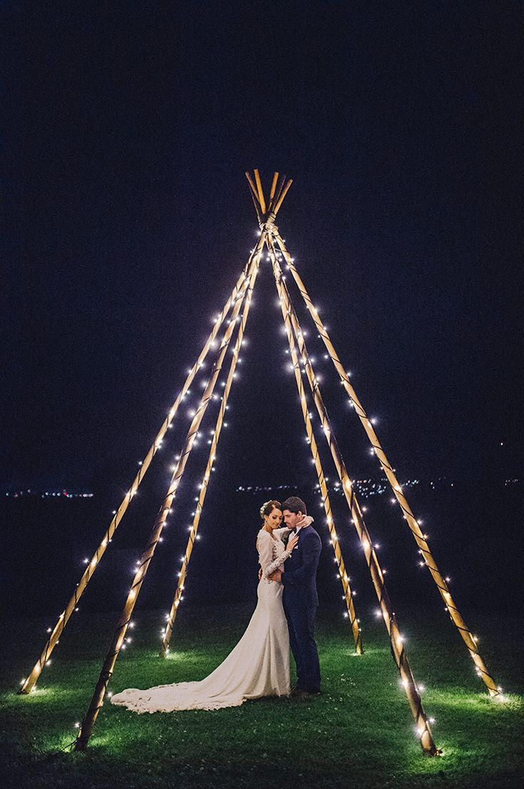 After dark wedding portraits beneath a naked tipi wrapped in fairy lights | Sophie Baker Photography