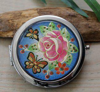 Metalen zakspiegeltje met vlinder en bloemen Mooi en handig zakspiegeltje. Met een druk op de knop opent zich het doosje, met daarin twee spiegeltjes. Eén ervan is een vergrotende spiegel.  Op de v...