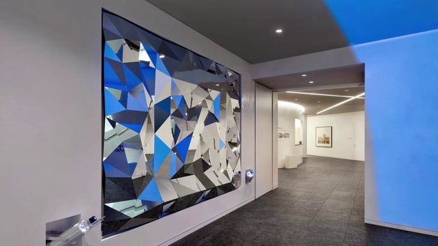 """""""Anamorphic Mirror"""" opens up the conference and brand area in the Deutsche Banks headquarters in Frankfurt. The installation is located at the end of a staircase. Consisting of a faceted mirror and blue light projected onto the opposite wall, it reflects the Deutsche Bank's logo when viewed from the sweet spot. Standing at the bottom of the stairs visitors initially see seemingly random blue reflections on the mirror's individual surfaces. Through their own movement visitors then generate a…"""