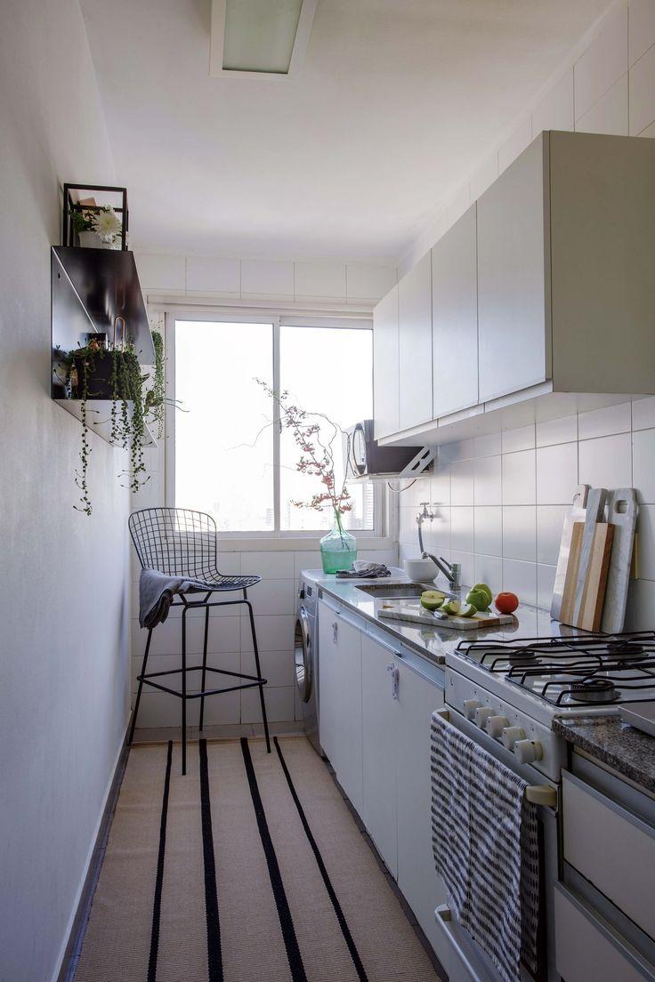 Cocina de un tríplex con alfombra lavable Capri (RUGit), estantería de chapa con terminación negro mate para frascos y especias, y una banqueta Bertoia, sobre la que hay un mantel de lino gris (Sissy Boy).