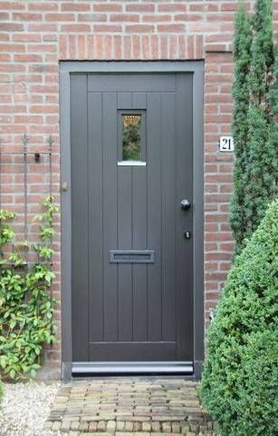 charcoal gray A soothing shade of gray effortlessly imparts the natural red brick exterior of this traditional home with a modern detail. Coupled with the bright greenery and the cobbled front path, the soft gray paint of the front door is the perfect fit.