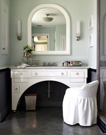 """""""The vanity is loosely based on a shapely black lacquer desk from the 1920s by Eileen Gray,"""" she says. """"It has a Deco feeling, but not slavishly so."""" She gave handblown glass sconces a machine-age shape. The ceiling light is 1940s Murano glass, from Carlos de la Puente. The swivel stool is from Ballard Designs. Mirrored wastebasket by Notre Monde."""