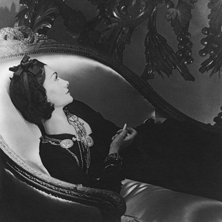 """""""Coco Chanel"""" by Horst P. Horst appeared in Vogue, February 1954. Chanel leans back on a couch, holding a cigarette. She wears a simple dark dress, gold medallion necklaces and a simple ribbon in her hair. She exudes the elegant simplicity that characterizes her brand to this day."""