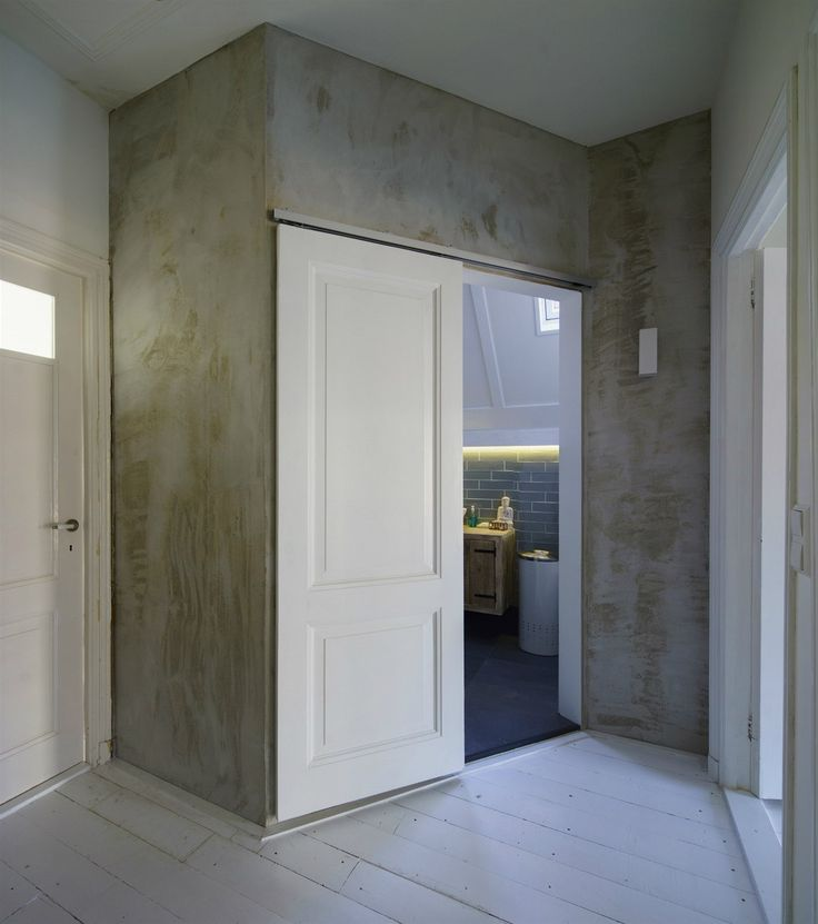 Betonová stěrka na stěnách koupelny jasně opticky vymezuje společný prostor určený pro hygienu.