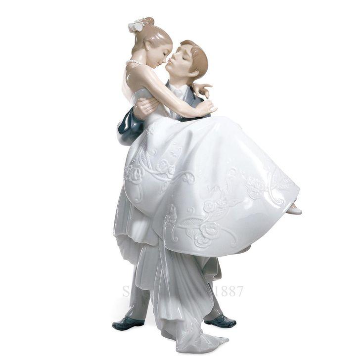 """Lladrò – Statua """"Il giorno più felice"""" L'amore profondo tra due giovani appena convolati a nozze. Lo sposo, teneramente, tiene in braccio lei dandole un bacio, un bacio pieno di affetto, di amore. Le espressioni bellissime dei due sposini sono ricche di dolcezza e premura. Regalo perfetto per giovani innamorati come segno di buon auspicio, per matrimoni o come ricordo speciale."""