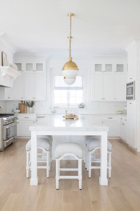 A Long White Kitchen Island Fitted With Legs Seats White Abacus Counter Stools Beneath A Thick Natural Stone Countertop Lit By Two Brass Hicks Pendants