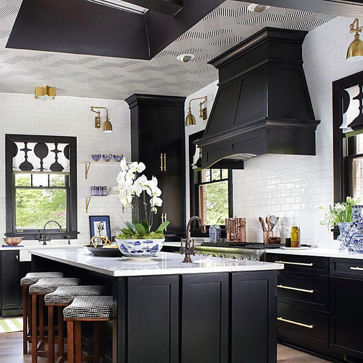 White subway-style tiles extend from the quartz countertops to the ceiling, defining the work zone and creating a clean backdrop that harkens to an early 1900s kitchen. Window fabrics are graphic Deco-like, black-and-white motifs that depict oversize champagne flutes stacked end-to-end.