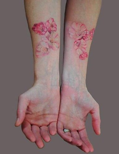 On the right hip around the waist and onto the right rib Cherry blossom tattoo. So charming.