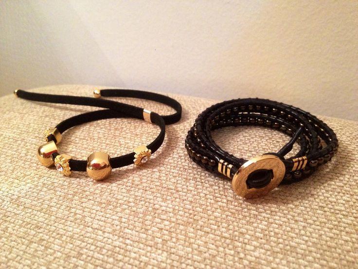 Kit com duas pulseiras: Uma pulseira modelo Chan Luu confeccionada com fio de couro preto e miçangas furta cor ouro velho bem escuro. Detalhes e botão dourados Uma pulseira em camurça com pingentes dourados e dourados com strass.