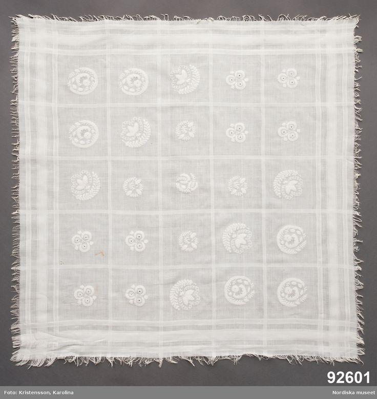 SE Södra Möre. Kvadratiskt huvudkläde av vit fintrådig bomullslärft, med invävda rutor i tätare kypertväv. Rutorna ca 15 x 15 cm, i varje ruta  ett broderat motiv i tambursöm med vitt bomullsgarn, 4 olika motiv. Runtom kort upprispad frans.  Det vanligaste är att dessa tambursömskläden har burits som huvuddukar.